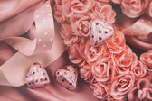 Heart made of pink roses with ribbons and chocolates on satin — Stock Photo