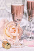 Ring in pink champagne with flowers — Stock Photo