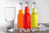 Three bottles with drinks with glass and ice — Stock Photo