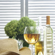 Stock Photo: Glass of wine standing on old table with straw hat