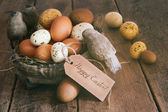 Assorted eggs in basket with note card — Stock Photo