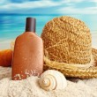 Straw hat with towel and lotion on the beach — Stock Photo