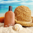 Straw hat with towel and lotion on the beach — Stock Photo #47743707