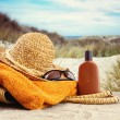 Straw hat with towel and lotion at the beach — Stock Photo