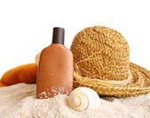 Straw hat with towel and suntan lotion on white — Stockfoto