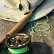 Close-up of fly-fishing reel and rod with hat — Stock Photo #47860797