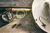 Fly fishing rod with hat on wood — Stockfoto