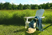 Jeans laying on adirondack chair in field — Stock Photo