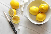 Fresh lemons and sugar cubes on marble counter  — Stock Photo
