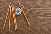 Pencils and lock on wood surface — Stock Photo