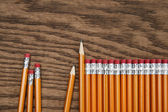 A row of red pencils on wood surface — Stock Photo