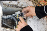 Electrician checks external electrical cable — Stock Photo