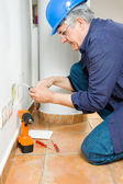 Electrician sets the socket — Stock Photo