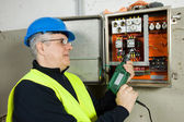 Eletricista sênior verificar painel elétrico — Fotografia Stock