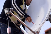 Man sets a satellite dish — Stockfoto