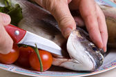 Chef with knife cuts the Sea bream — Stock Photo