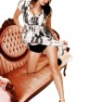 Girl kneeling on sofa. — Stock Photo