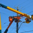 Lift trucks on power lines. - Stock Photo