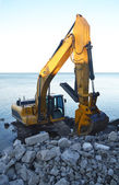 A backhoe on the lake. — Stock Photo