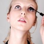 Blond girl fixing her eyelashes. — Stock Photo #3191321