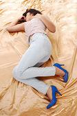 Girl lying on gold fabric. — Stock Photo