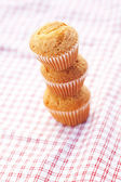 Three muffins on plaid fabric — Stock Photo
