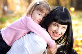 Beautiful young mother holding her daughter on back — Stock Photo