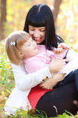Beautiful young mother kissing her daughter in autumn forest — Stock Photo