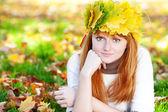 Femme adolescent jeune rousse dans une guirlande de feuilles d'érable allongé o — Photo