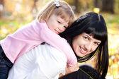 美丽的年轻母亲和她的女儿躺在秋天树叶上 — 图库照片