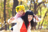 Beautiful young mother holding her daughter in a wreath of maple — Stock Photo