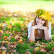 Young redhead teenager woman in a wreath of maple leaves lying o — Stock Photo