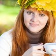 Young redhead teenager woman in a wreath of maple leaves with cu — Stock Photo
