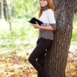 Stock Photo: Portrait of beautiful young redhead teenager womreading b