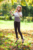 Jumping young redhead teenager woman in the forest — Photo