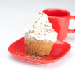 Muffin with whipped cream and red cup on white background — Stock Photo