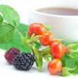 Royalty-Free Stock Photo: Cup of tea, blackberry,raspberry and rosehip berries with leaves