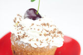 Muffin with whipped cream and cherry on white background — Stock Photo
