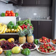 Stock Photo: Abundance of fruits and vegetables in kitchen