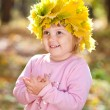 Beautiful little girl in a wreath of maple leaves in autumn fore - Stock Photo