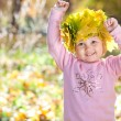Stock Photo: Beautiful little girl in a wreath of maple leaves in autumn fore