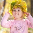 Royalty-Free Stock Photo: Beautiful little girl in a wreath of maple leaves in autumn fore