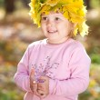 Beautiful little girl in a wreath of maple leaves in autumn fore — Stock Photo