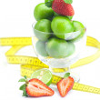 Lime in a glass cup, measuring tape, strawberry and mint isolate - Stock Photo