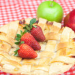 Apple pie, apple, lime, cinnamon and strawberry on plaid fabric - Stock Photo