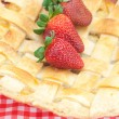 Apple pie and a strawberry on plaid fabric - Stock Photo