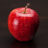 Red apple on a wooden table — Stock Photo