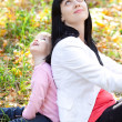 Beautiful young mother and her daughter looking up in the autumn — Stock Photo