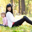 Beautiful young mother and her daughter sitting on the autumn le — Stock Photo
