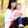 Beautiful young mother and her daughter on the autumv forest — Stock Photo